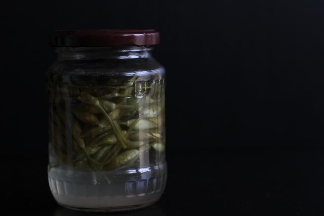 Fermented ramson flower buds in a jar