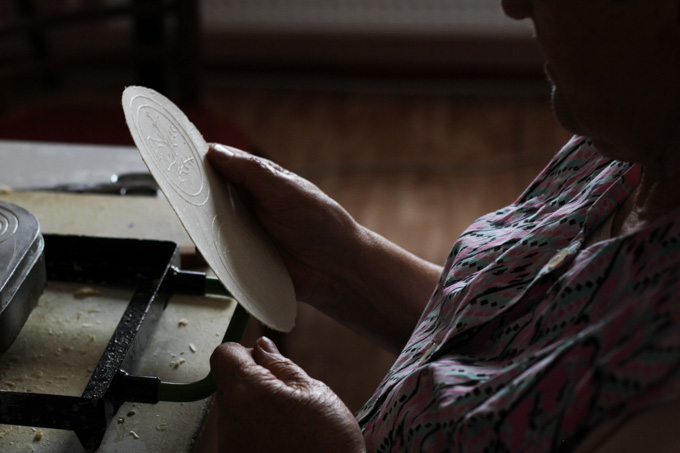 A woman holds oplatky, also called oblatky, as she makes them