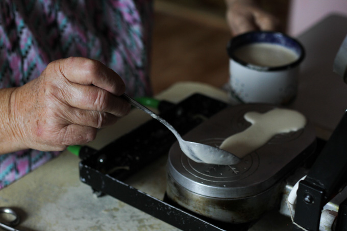 An older woman spreads batter to make Slovak Christmas wafers
