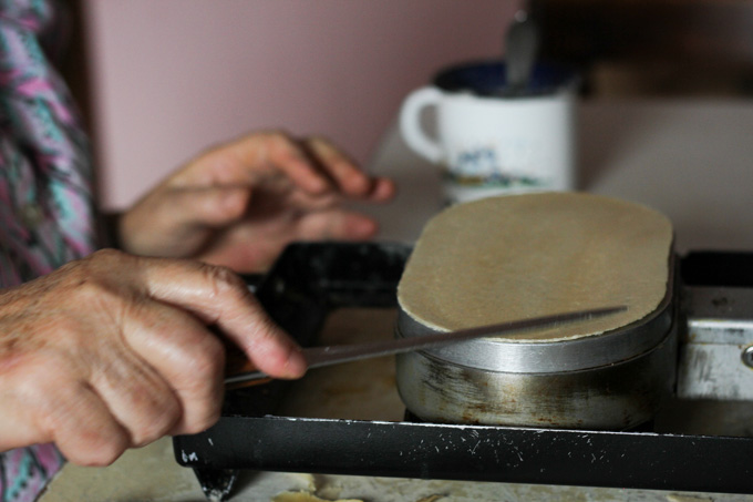 A Slovak woman trims the edge of the oblatky with a thin knife