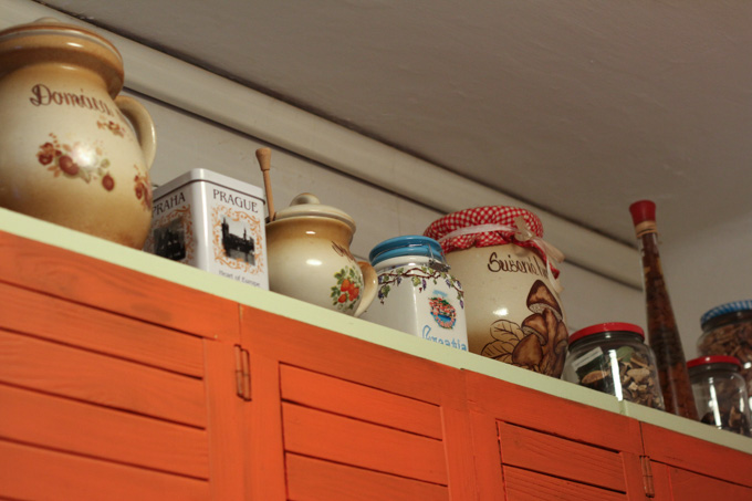 On top of the kitchen cabinets are various containers
