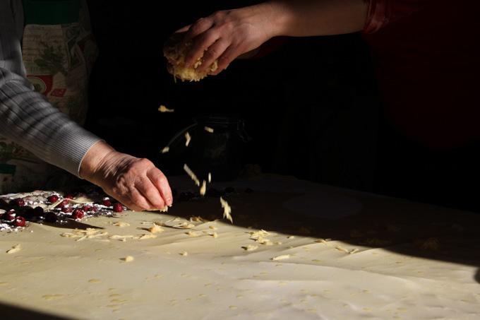 Sprinkling grated apple on pulled strudel dough