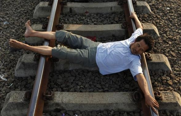 A man lies on railway tracks in Rawa Buaya in Indonesia's West Java province