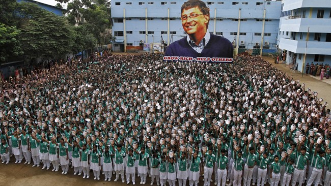 School children hold portraits of Microsoft co-founder Bill Gates in front of a giant picture of Gates during celebrations to mark his 60th birthday inside the school premises in Chennai, India, October 28, 2015. REUTERS/Stringer