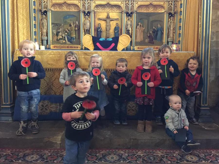 Children holding poppies they have made for Remembrance Day