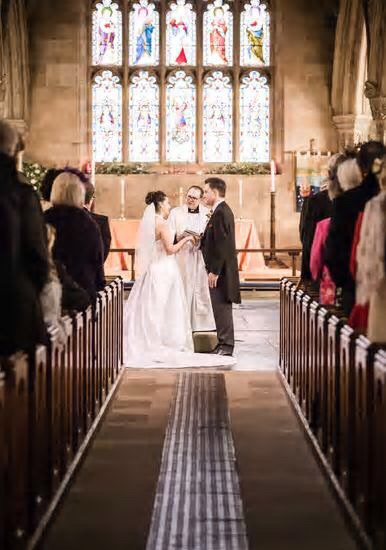 A bride and groom holding hands in front of a Vicar at St Michael's Church