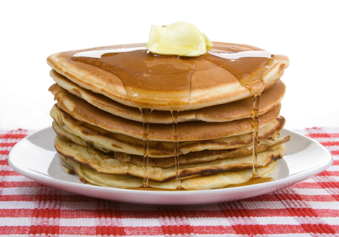 An image of a pile of pancakes with butter and syrup on a plate on a chequered tablecloth