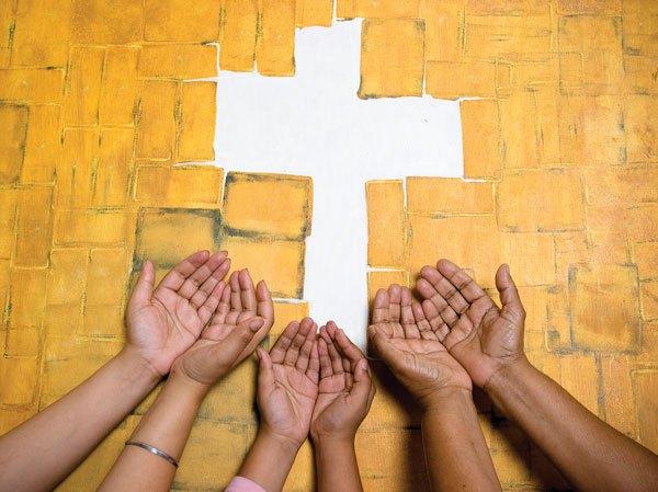 Image of hands reaching toward a cross