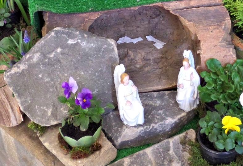A photograph of an open tomb in an Easter garden