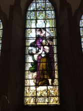 """Stained glass window depicting """"Charity"""" at St Peter the Fisherman, Craster"""
