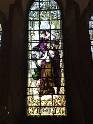 "Stained glass depiction of ""charity"" at St Peter the Fisherman, Craster"