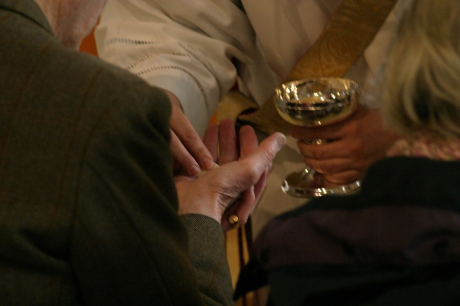 A photograph of a vested priest handing a Communion wafer into an outstretched hand