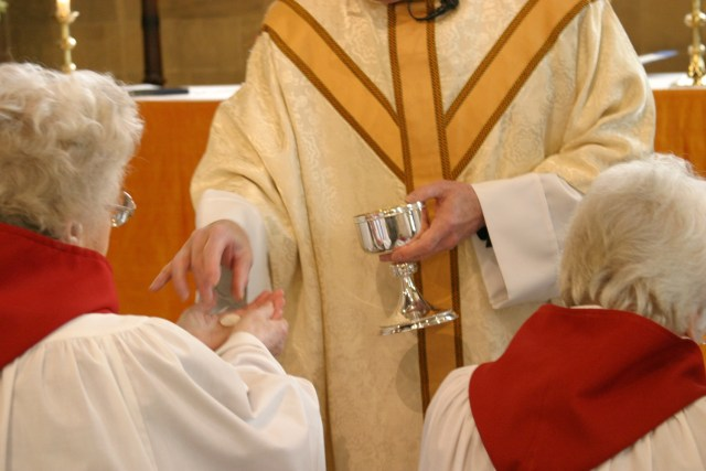 An image of a Priest distributing Communion to a chorister at St Michael's