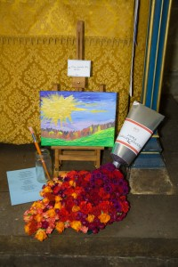 A flower arrangement in St Michael's Church, showing a canvas and flowers spilling out from a tube of paint