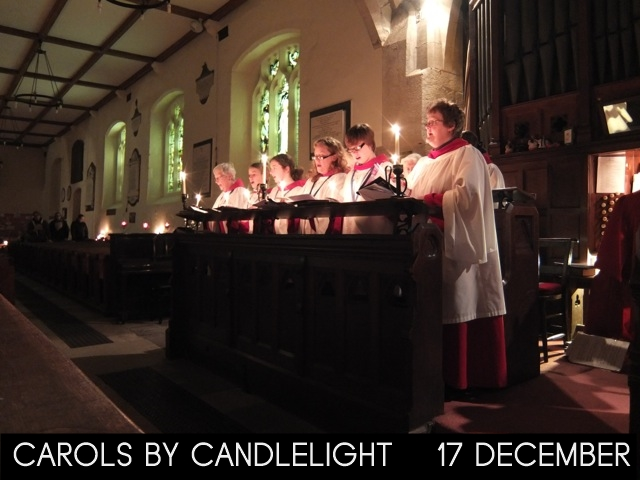 """A photograph of St Michael's robed choir holding candles with the words """"Carols by Candlelight 17 December"""""""