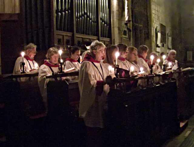 A photograph of a robed choir singing, lit by candles