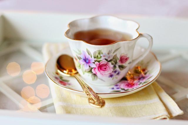 A photograph of a flowery, china cup with tea in it, standing on a saucer
