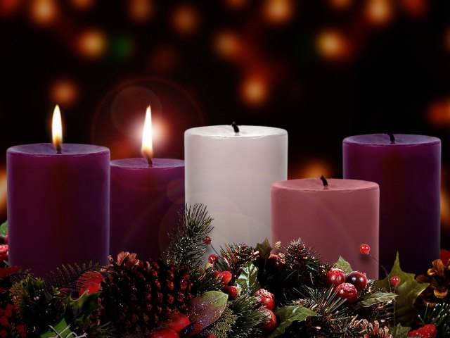 A photograph of three purple candles, one pink candle, and a white candle. Two of the purple candles are lit.