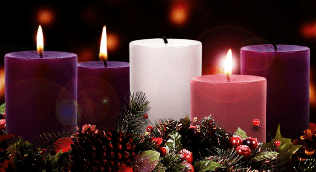 A photograph of three purple candles, one white candle, and a pink candle. Two purple candles and a pink candle are lit.