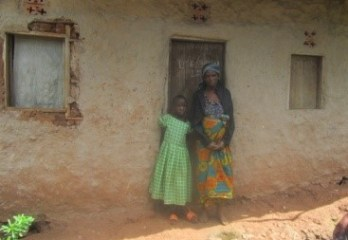 woman and daughter standing outside their house