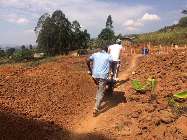 Man pushing wheelbarrow on a building site