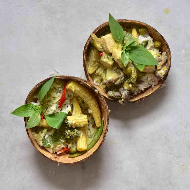 Green Thai curry served in coconut bowls