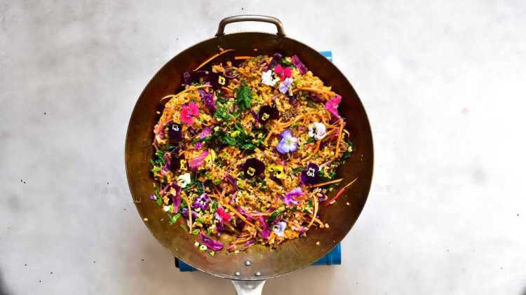 Homemade vegetarian bibimbap decorated with edible flowers