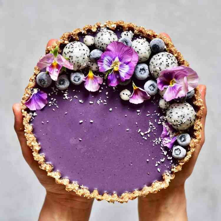 healthy refined sugar free, raw vegan earl grey blueberry tart with dragon fruit and edible flowers