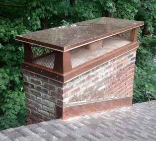 chimney cap on top of brick chimney