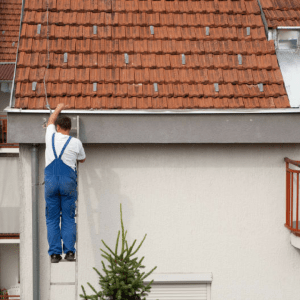 man climbing ladder to get on roof