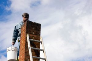 man on ladder with bucket next to chimney