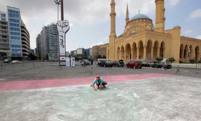 Attempting to enter the Guinness Book of Records: An artist draws with chalk the largest Lebanese flag