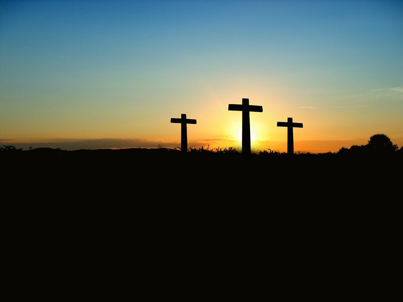 Three crosses on a hillside at sunset.