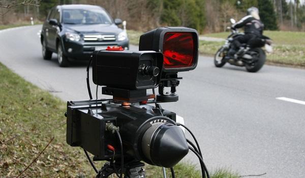 A car and a motorbike pass next to a radar device during a speed check on the Route du Mollendruz in Mont-la-Ville, 60 kilometres (37 miles) west of Geneva April 7, 2009. REUTERS/Denis Balibouse(SWITZERLAND POLITICS CRIME LAW) - RTXDQQ7
