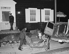 Police remove bodies from the Amityville Horror house