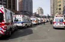Ambulances, many of which were already on scene for runners, wait in line to pick up victims