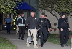 Police exiting an apartment where they searched for evidence related to the bombing