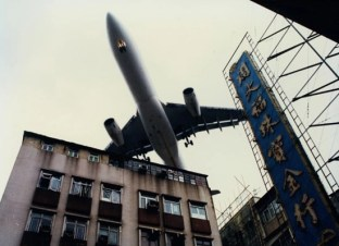 Plane flying between buildings on its approach to Kai Tak Airport