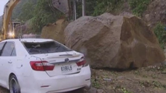 Mudslide and massive boulder that narrowly missed passing car