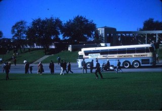 Skaggs photo showing press bus following motorcade to Parkland Hospital - grassy knoll visible in background