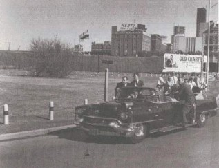 President limo approaching the Stemmons-Freeway ramp - School book depository visible in background.