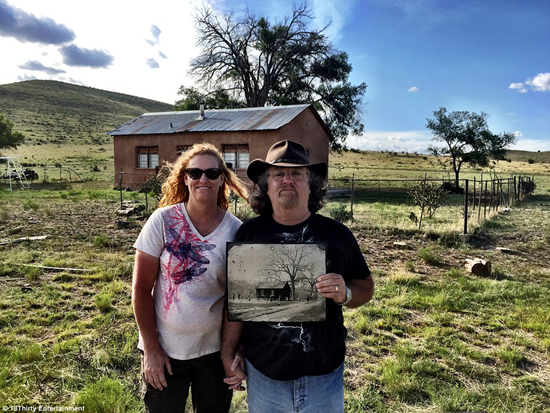Randy Guijarro and his wife holding original photo of New Mexico schoolhouse while standing in front of the schoolhouse discovered on New Mexico ranch
