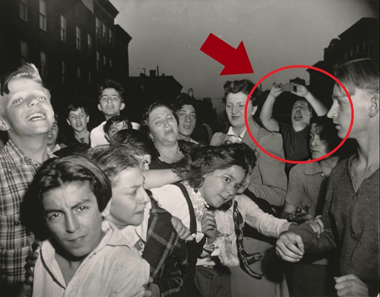 Man in old photo appears to be taking a picture with a modern-day cellphone