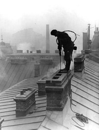 Chimney sweep lowers child into chimney