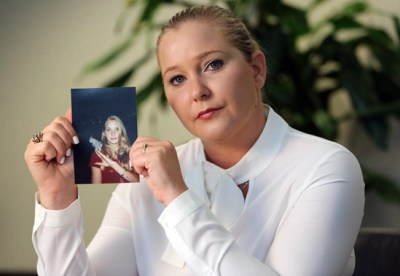 Virginia Roberts holding photo of herself at 16