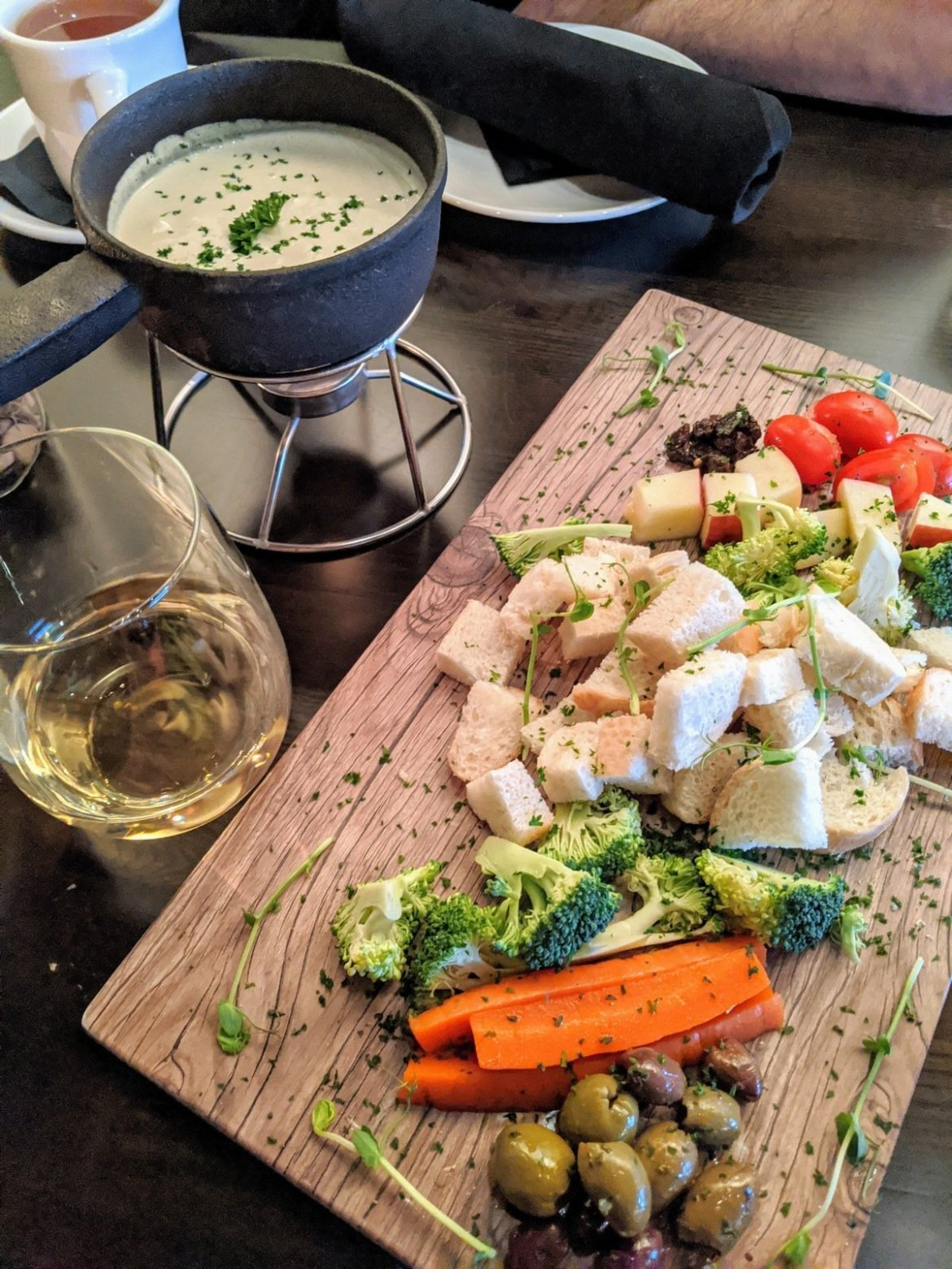 vegan fondue, a glass of wine and a tray of veggies