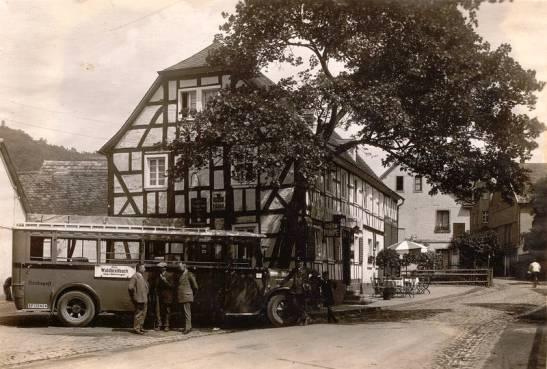 """Seit 1923 war vor dem """"Schützenhof"""", der sich inzwischen zu einem beliebten bürgerlichen Gasthof gemausert hatte, eine wichtige Haltestelle der """"Kraftpostlinie"""" eingerichtet worden. Auf dem Bild sehen wir einen für die damalige Zeit modernen Post-Omnibus der Linie """"Linz-Hönningen-Waldbreitbach"""". Von links nach rechts haben sich der """"Gastwirth Willi Schmitz"""", der """"Alt-Vorsteher Josef Kröll"""" und der """"Kaufmann Peter Reuschenbach"""" Zeit genommen für ein kleines Schwätzchen. Rechts außen ist der Postschaffner Stephan Kröll zu erkennen. (Richard Schicker 1997)"""