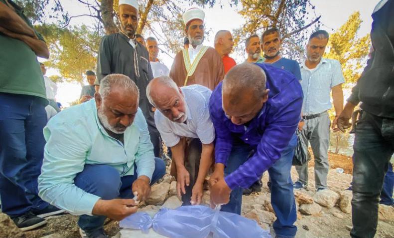 المواطنين يعيدون دفن رفات الأموات في المقبرة اليوسفية بعد أن تسبب الاحتلال بنشبها