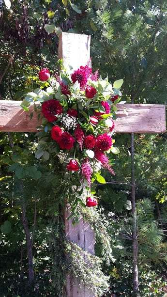 wooden cross with fresh flowers