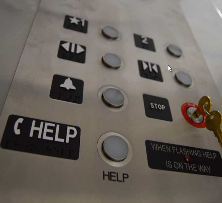 """Negative interest rates symbolized by upward view of elevator buttons. The word """"HELP"""" is prominent at  bottom."""
